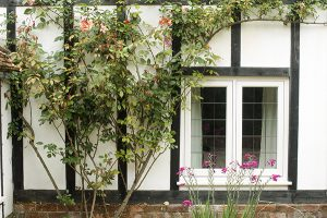timber windows on a black and white cottage