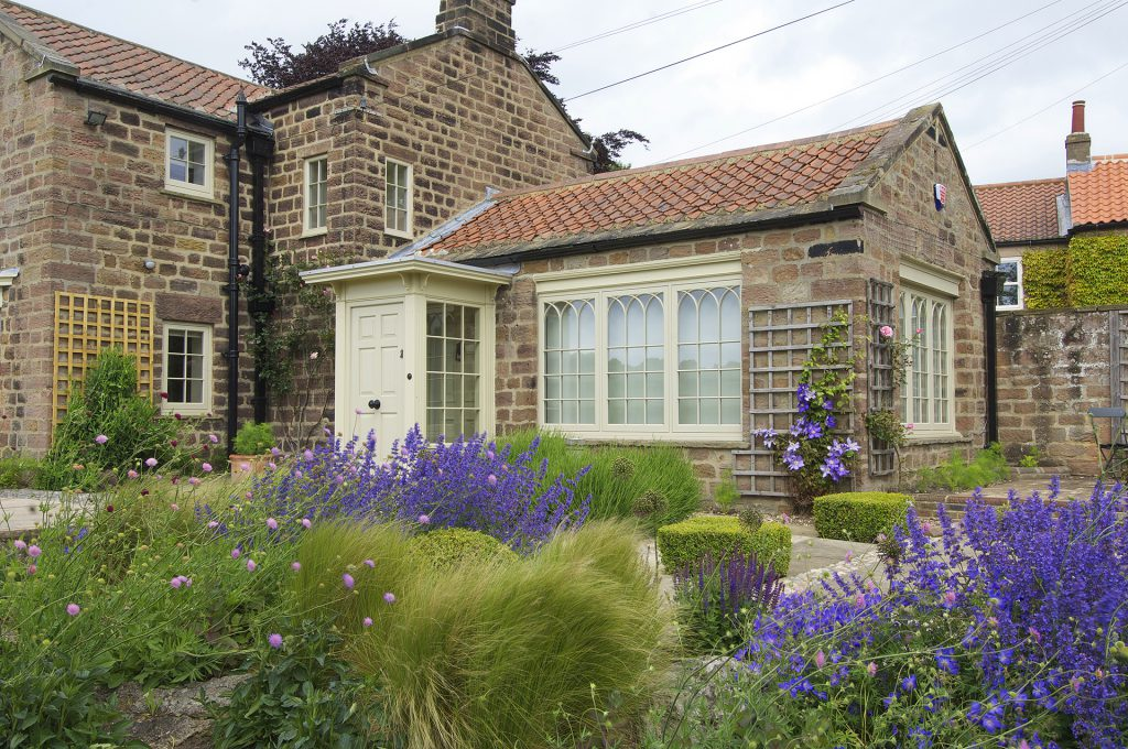 property showing cream windows and doors with a garden in the foreground