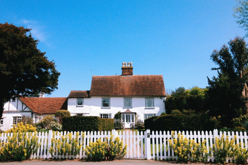 period cottage with white picket fence and bright blue sky